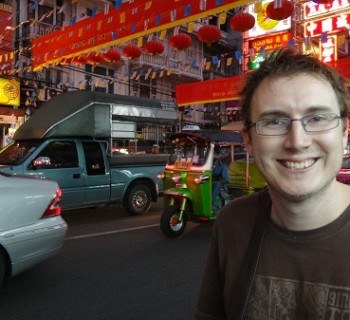 Andrew sitting at a roadside Noodle Soup Stall in Bangkok's China Town